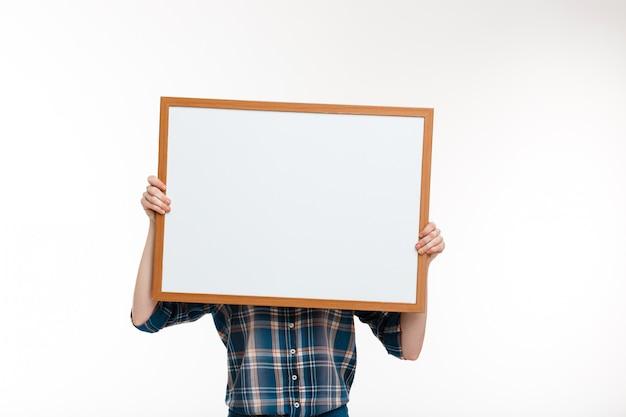 Belle fille au gingembre avec tableau blanc sur mur blanc.