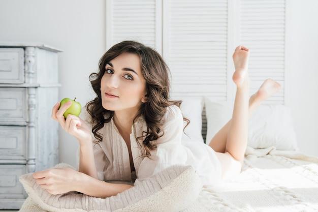 Belle fille au lit et tenant une pomme