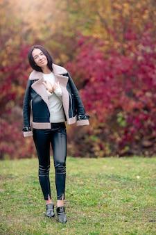 Belle fille en automne parc en plein air sur une journée ensoleillée