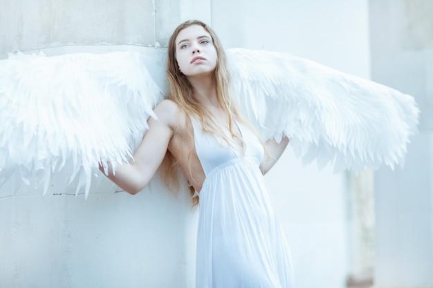 Belle fille aux ailes blanches debout près d'un mur blanc