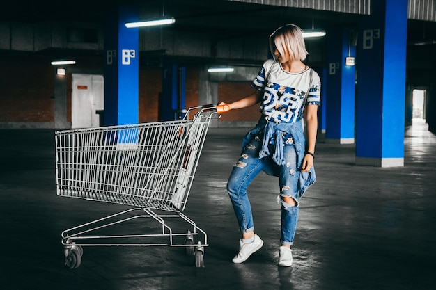 Belle fille aux cheveux blancs courts vêtue d'un jean avec des caddies dans le parking