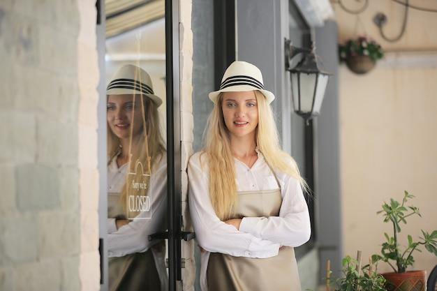 Belle fille aux cheveux blonds debout près de la plaque d'enseigne du magasin cloesd à la porte avec confiance devant le café.