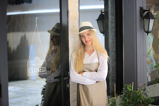 Belle fille aux cheveux blonds debout près de la plaque d'enseigne ouverte à la porte avec confiance devant le café.