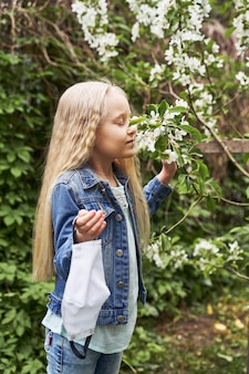 Une belle fille aux cheveux blonds a enlevé son masque et renifle un arbre en fleurs au printemps