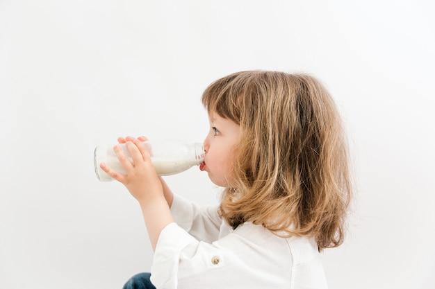 Belle fille aux cheveux bouclés et aux yeux bleus boit du lait d'une bouteille.