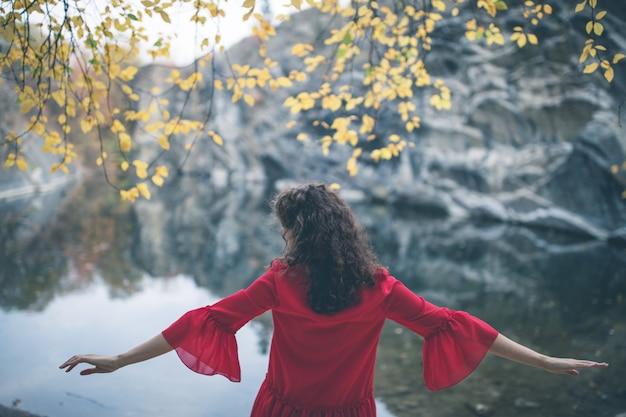 Belle fille aux cheveux bouclés dans une robe rouge au bord du lac à bras grands ouverts.