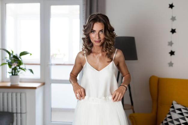 Une belle fille aux cheveux bouclés, une future mariée mesurant une robe de mariée chez elle avant le mariage.