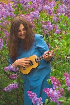 Belle fille aux cheveux bouclés vêtue d'une robe en jean jouant du ukulélé