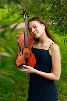 Belle fille aux cheveux bruns d'apparence asiatique avec un violon dans la nature. musicien de nature. musique classique. photo de haute qualité