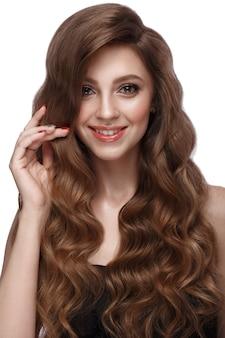 Belle fille aux cheveux bruns avec des cheveux parfaitement bouclés et un maquillage classique