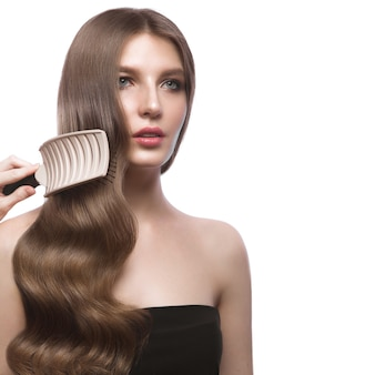 Belle fille aux cheveux bruns avec des cheveux parfaitement lisses et un maquillage classique.