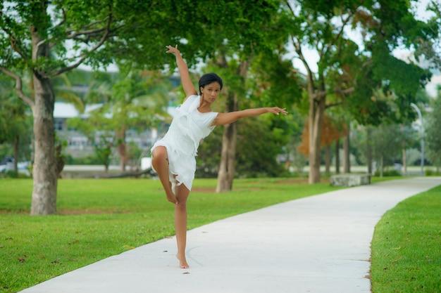 Une belle fille aux cheveux courts noirs dans une pose de danse vêtue d'une robe blanche