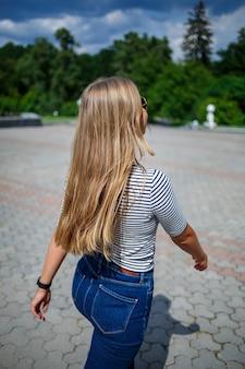Une belle fille aux cheveux longs blonds d'apparence européenne. vêtu d'un jean et d'un t-shirt. marcher par une journée ensoleillée