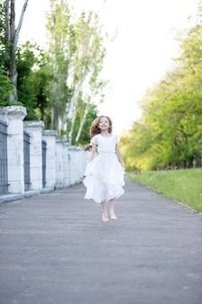 Une belle fille aux cheveux longs blonds dans une robe de soie blanche délicate rebondit comme si elle volait au-dessus de la route