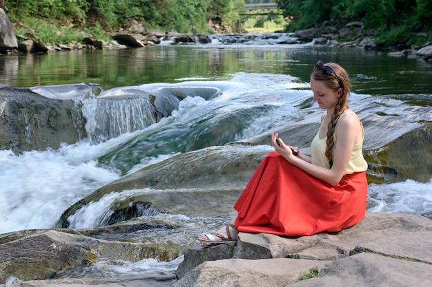 Belle fille aux cheveux longs dans une jupe rouge avec un smartphone assis sur un rocher sur un mur de cascade de rivière de montagne. soirée d'été. tranquillité et jouissance de la nature