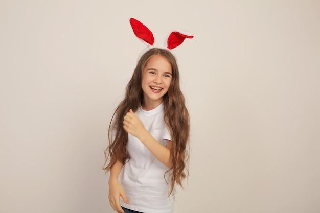 Une belle fille aux cheveux longs dans un tshirt blanc avec des oreilles de lapin sourit pâques