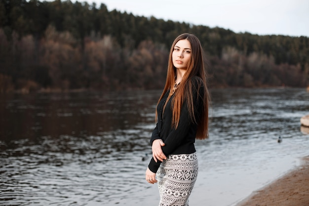 Belle fille aux cheveux longs debout près de la rivière par une journée ensoleillée