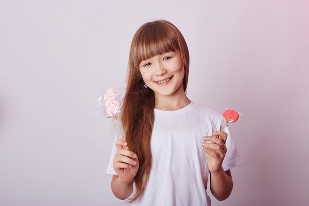 Belle fille aux cheveux longs mange lollipop caramel