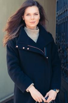 Belle fille aux cheveux longs en manteau noir à l'extérieur
