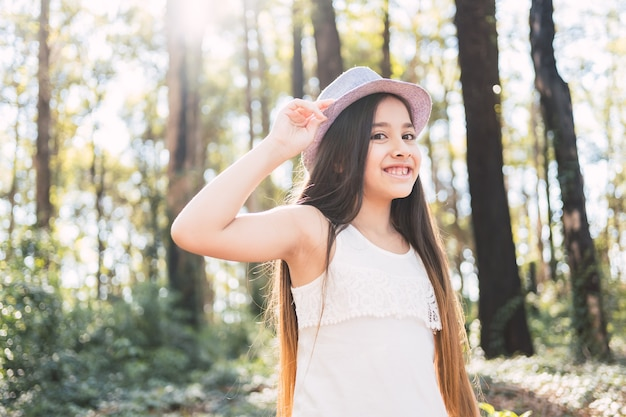 Une belle fille aux cheveux longs portant un chapeau à l'extérieur.