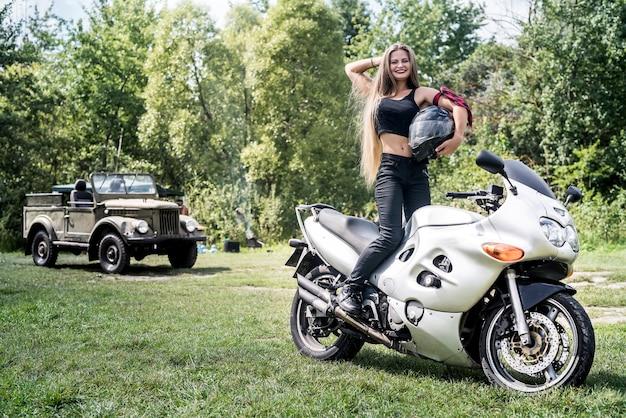 Belle fille aux cheveux longs posant sur une moto