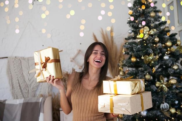 Belle fille aux cheveux longs près de l'arbre de noël tenant des boîtes dorées avec des cadeaux et souriant à la caméra