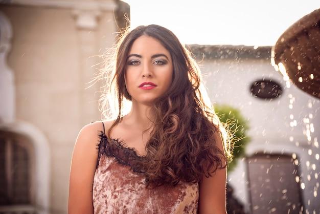 Belle fille aux cheveux longs en regardant la caméra avec la lumière du soleil derrière elle