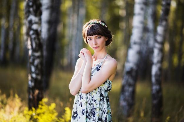 Belle fille aux cheveux noirs et aux yeux bruns avec une couronne sur la tête dans une robe d'été sur fond vert. la femme dans la forêt par une journée ensoleillée. modèle posant sur la nature.