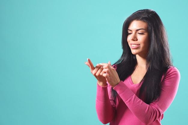 Belle fille aux cheveux noirs fait un vœu et plie ses doigts sur sa main