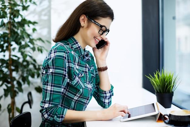 Belle fille aux cheveux noirs portant chemise et lunettes assis dans un café avec tablette et tasse de café, tenant un téléphone mobile, concept indépendant, souriant.