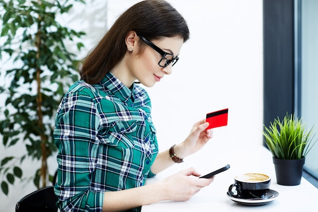 Belle fille aux cheveux noirs portant chemise et lunettes assis dans un café avec téléphone portable et tasse de café, tenant une carte de crédit, achats en ligne.