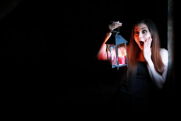 Belle fille aux cheveux rouges avec une lanterne dans une pièce sombre