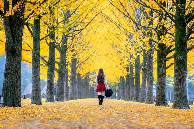 Belle fille aux feuilles jaunes sur l'île de nami, en corée.