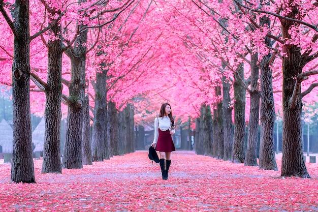 Belle fille aux feuilles roses dans l'île de nami, corée du sud