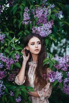 Belle fille aux grands yeux près de l'arbre de lilas.