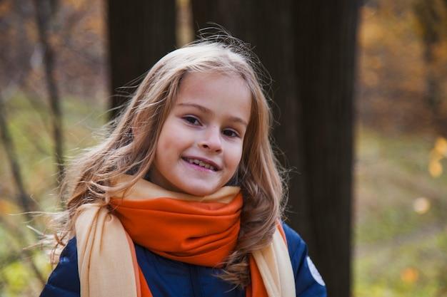 Belle fille aux longs cheveux blonds dans le parc en automne. fille aux yeux bruns avec des tresses dorées sur fond de feuilles d'automne jaunes