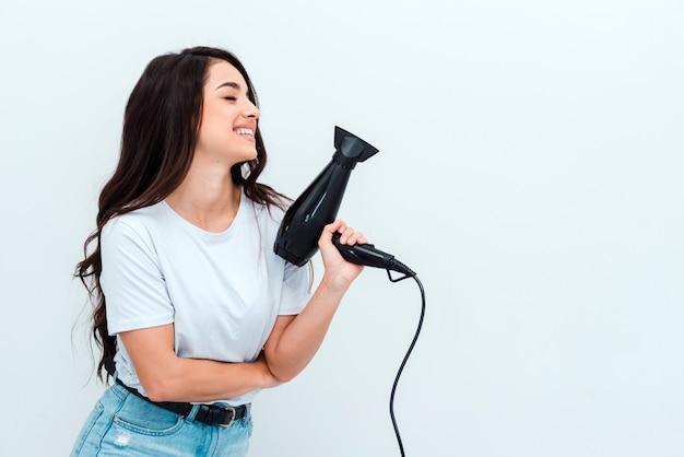 Belle fille aux longs cheveux noirs détient un sèche-cheveux
