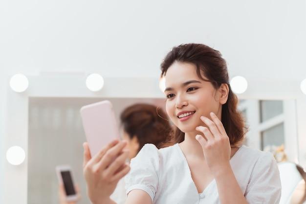 Belle fille aux longs cheveux noirs prenant des selfies devant le miroir.