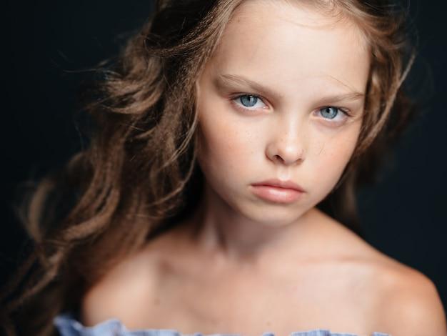 Une belle fille aux yeux bleus avec des épaules nues sur une chevelure foncée et bouclée