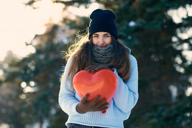 Belle fille avec ballon en forme de coeur dans les mains, saint valentin