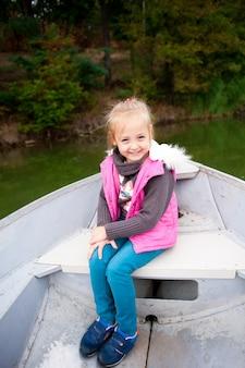 Belle fille sur un bateau sur le lac