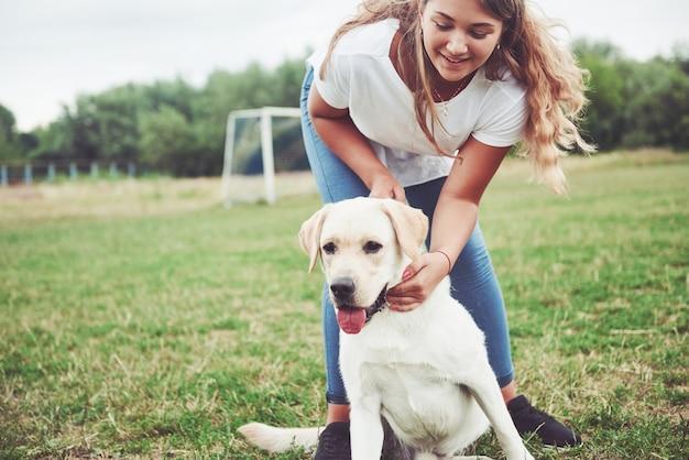 Belle fille avec un beau chien dans un parc sur l'herbe verte.