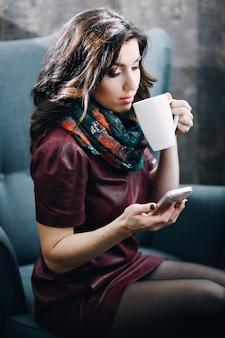 Belle fille avec un beau maquillage, boire du thé ou du café au café et en regardant le téléphone. discuter en ligne avec un ami, correspond à un ami, jeune femme buvant du thé, du café et discuter en ligne