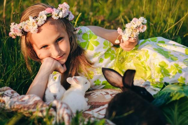 Belle fille blonde allongée sur l'herbe avec des lapins.