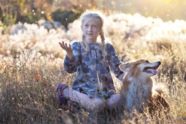 Belle fille blonde amusante et corgi moelleux dans le parc en automne.