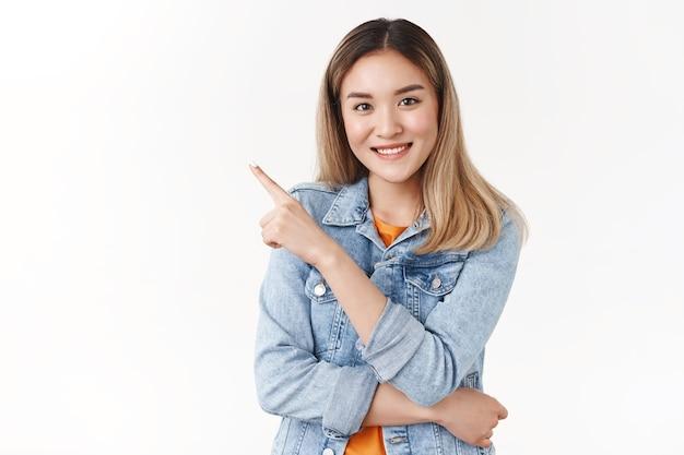 Une belle fille blonde asiatique élégante et confiante recommande de suivre sa direction en pointant l'index dans le coin supérieur gauche de la caméra souriante mur blanc sûr de lui