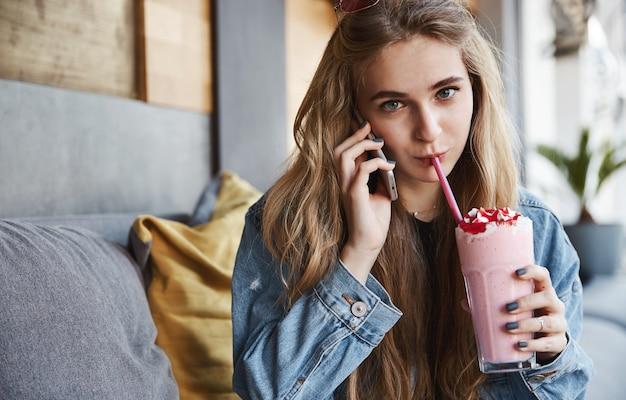Belle fille blonde assise dans un café et boire un smoothie, parler