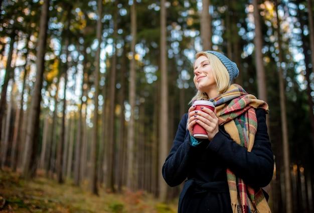 Belle fille blonde au chapeau bleu avec une tasse de café dans une forêt