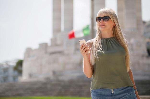 Belle fille blonde aux cheveux longs, tenant le smartphone à la main, marchant dans la rue italienne à la journée d'été ensoleillée.
