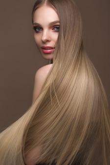 Belle fille blonde aux cheveux parfaitement lisses, maquillage classique, visage beauté
